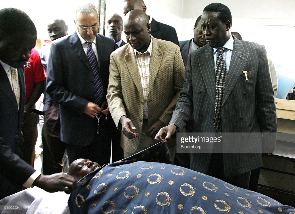 Raila Odinga, leader of the Orange Democratic Movement, right, along with colleagues pay their respects to David Kimutai Too, a politician who was shot in the western  town of Eldoret, as his body lies in Nairobi, Kenya, on Friday, Feb.1, 2008. United Nations Secretary-General Ban Ki-Moon arrived in Kenya to bolster peace talks aimed at ending post-election violence that has killed more than 800 people. Photographer: Boniface Mwangi/Bloomberg News